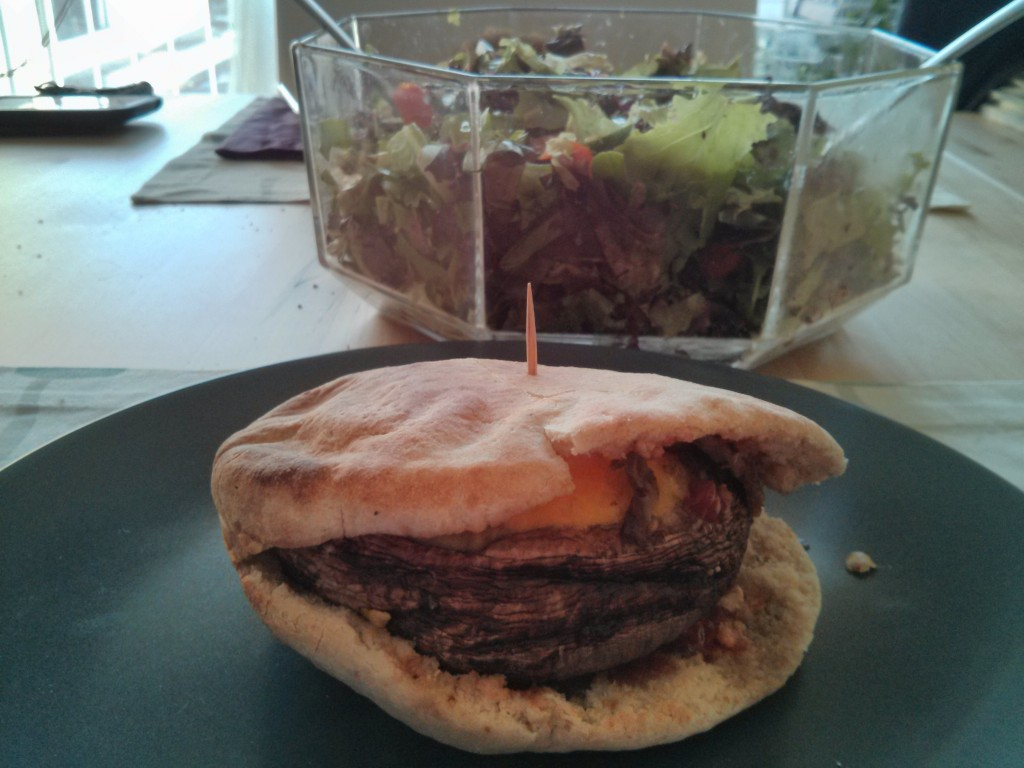 Portobello burger with salad in the background