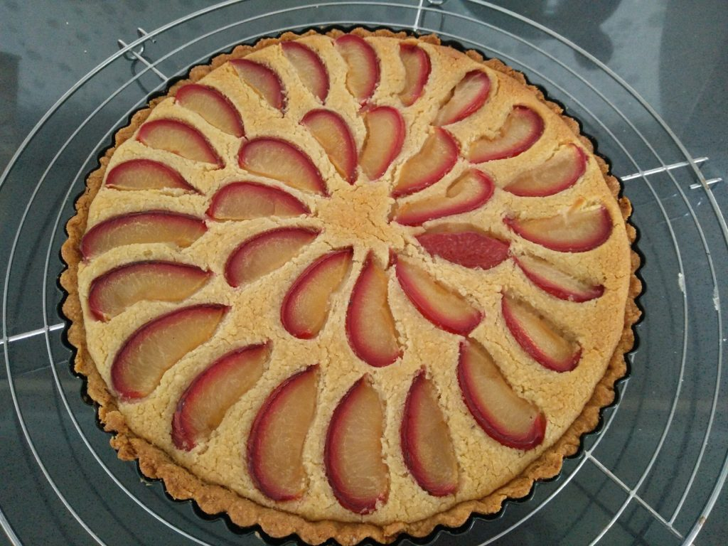 Picture of a plum frangipane tart still in its mold, resting on a cooling tray, on a dark kitchen counter